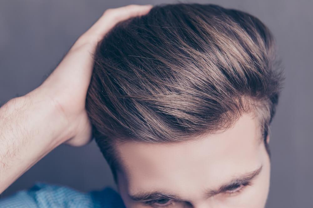 髪をかき分ける男